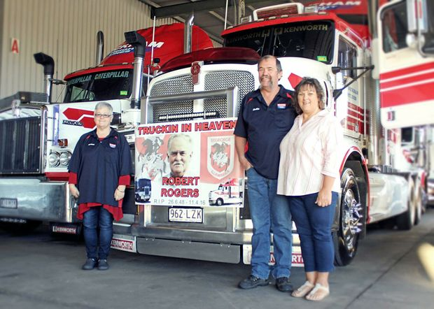 KEEP TRUCKIN: Diann Tysoe, with the banner of her late partner Robert Rogers, and truck driver Robbie Larfield and his wife Rosie.