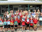 BOOKS UPON BOOKS: The staff, students and parents of Comet State School with a handful of books donated by DHL.