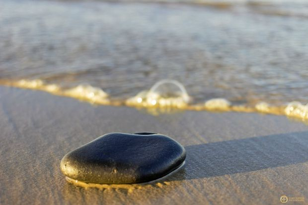 CLARITY: The tide washes in over a smooth stone at Cabarita.