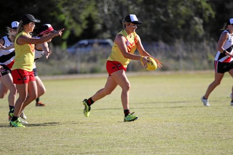 Action from the women's division at the Byron 9s AFL tournament, the Burleigh Bombers (yellow) versus Once Were Warriors (white).
