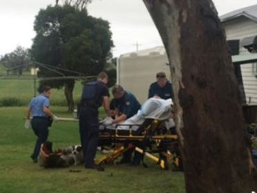 Paramedics treat a man for chest injuries after he was pinned to the ground during this afternoon's severe storm event.