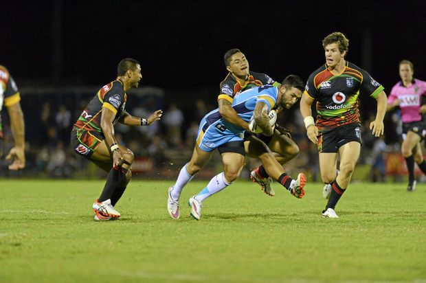 Titans player Jai Ingram is tackled in the NRL pre-season trial against Warriors at Clive Berghofer Stadium, Saturday, February 7, 2015. Photo Kevin Farmer / The Chronicle