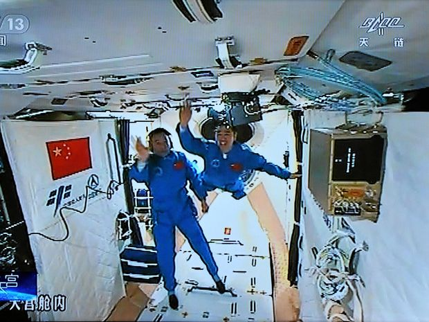NEW FRONTIER Chinese astronauts Jing Haipeng and Chen Dong wave to the camera after entering China's space lab Tiangong 2 from the manned spacecraft Shenzhou 11.