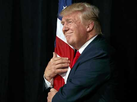 Republican presidential candidate Donald Trump hugs an American flag as he arrives to speak to a campaign rally, Monday, Oct. 24, 2016, in Tampa, Fla. (AP Photo/ Evan Vucci)