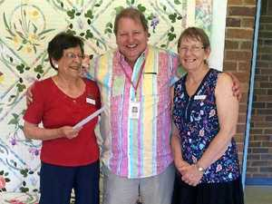 Smiles all around after quilting donation and prize
