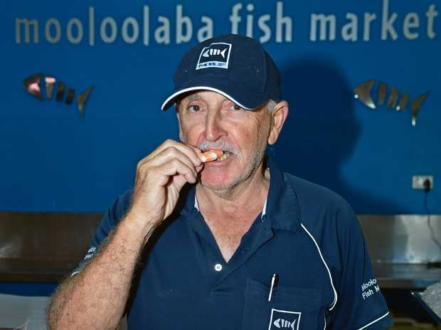 Tony Pizone of Mooloolaba River Fisheries eats one of his delicious prawns.