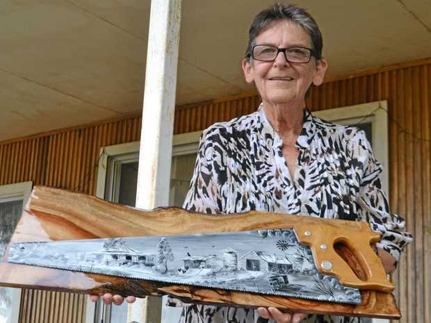 FOR THE LOVE OF ART: Brigalow-artist Jan Ferguson outside her home and studio with one of the painted hand saws she's become known for. It will be among the art works exhibited at Our Voice Through Art at Gallery 107 Dalby.