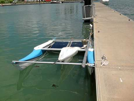 The catamaran which capsized off the Capricorn Coast is fastened to the pontoon at the Rosslyn Bay Harbour.