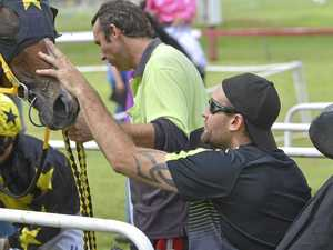 WINNER'S LUCK: Trainer Darryl Johnson gives his filly Rose or Bud a pat in the winning stall after she took out the Landmark QTIS Maiden Plate.