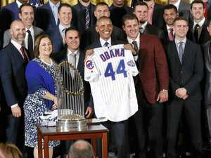President Barack Obama holds up a personalised Chicago Cubs baseball jersey presented to him by the team at the White House.