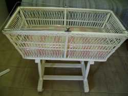 Cane bassinet fixed to wooden base on castors, net frame, mattress, embroidered sheets, pillow cases...