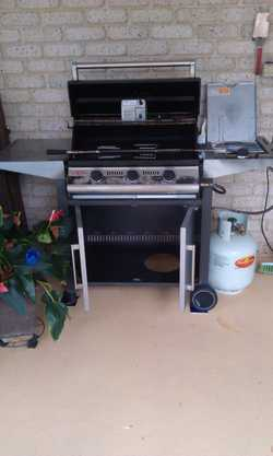 3 burner hooded with side burner spit roast attachments cupboard space below.
