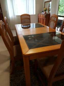 EXTENDABLE DINING TABLE.  SMOKED GLASS WITH LIGHT COLOUR HARDWOOD.   6 Rattan backed chairs.   EXTEN...