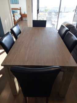 Brand new solid timber dining table and 6 black leather chairs. Table is brand new and has never bee...