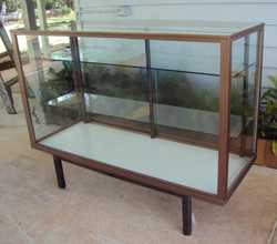 Alloy frame 1220W x 460D x 940mmH.  Glass to ALL sides.  Two (2) adjustable glass shelves.  Minor sc...