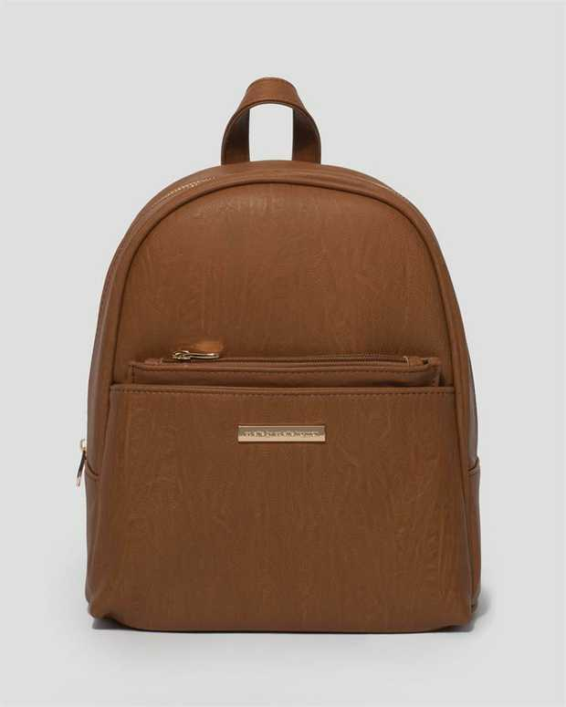 Part of our Backpack collection Tan finish with gold tone hardware Smooth faux leather Zip around...