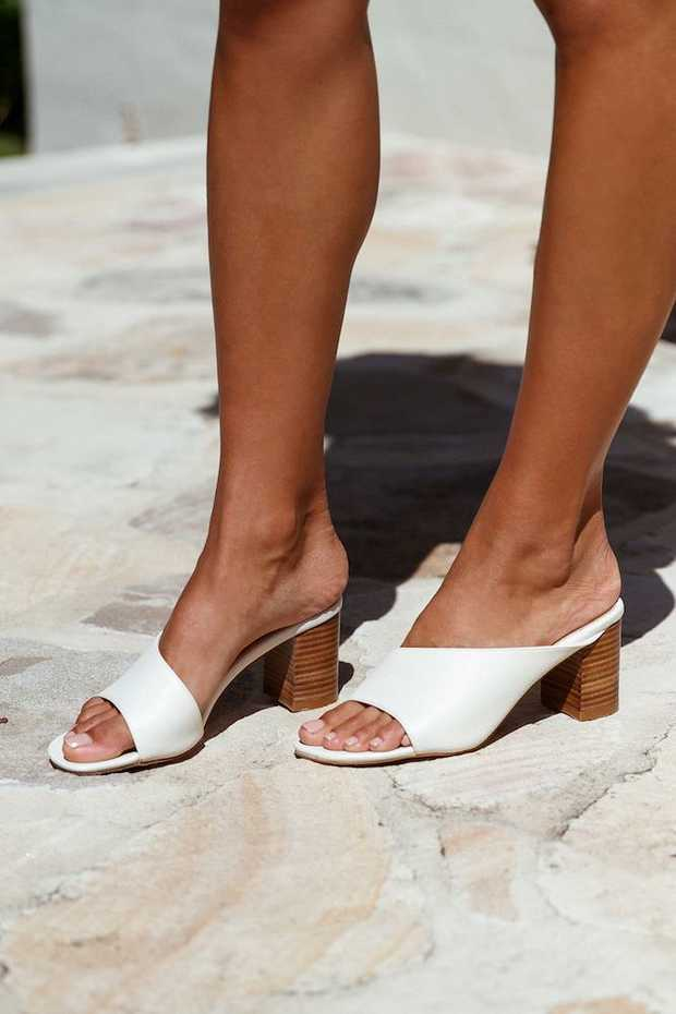 Off-white mule.  Non-leather upper; leather lining. Non-leather sole. Approx 5mm sole. Heel is...
