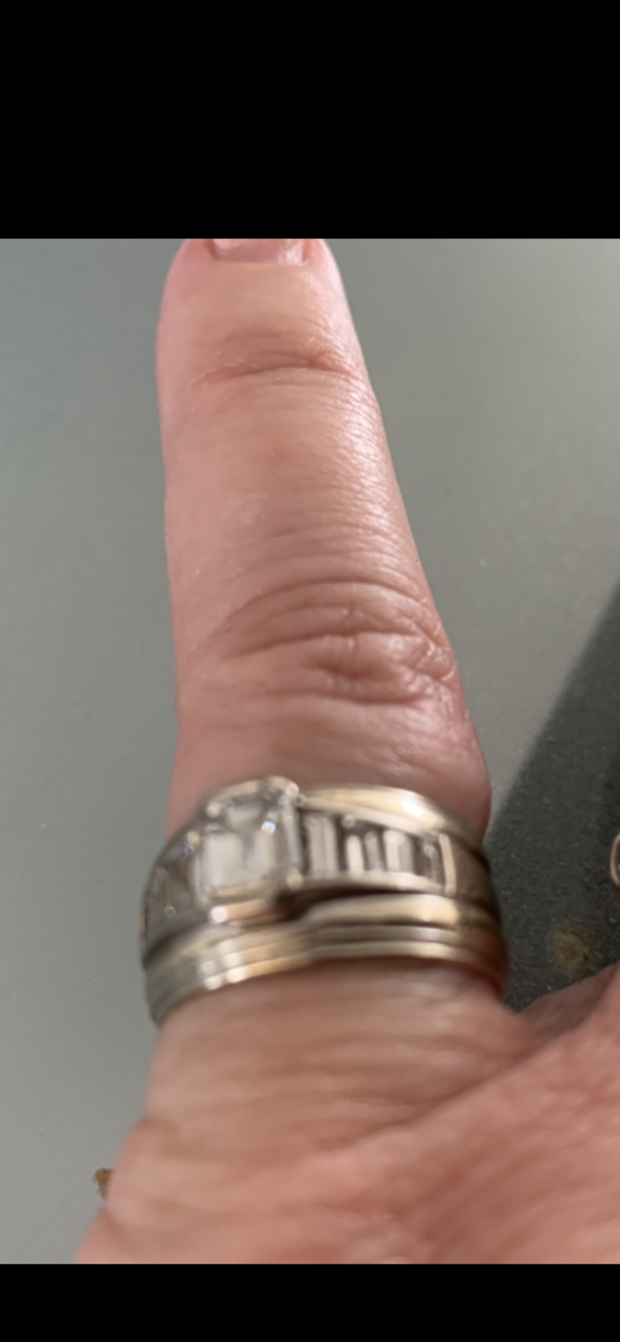 A wide, silver banded wedding ring with diamonds in the middle.  Extremely sentimental value as it...