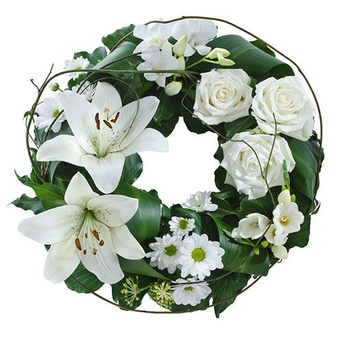 This floral wreath features beautiful blooms in tasteful white with lush green foliage. A beautiful...