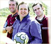 BEATING THE ODDS: Coolum  soccer players John Hatfield and Simon Gerbic flank coach Richard Hudson.Photo: Nicholas Falconer