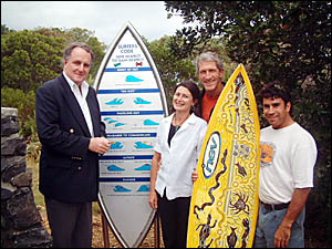 Mr Debus (left), Cr Barham, Nat Young and Sean Kay who is holding a surfboard he has just finished painting, with the new sign