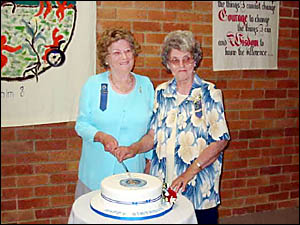 Gwen Stanford and Elnor Bostock cut the birthday cake