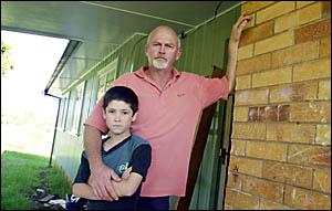 John Rixon and his  son Ben, outside their asbestos contaminated Lismore home.