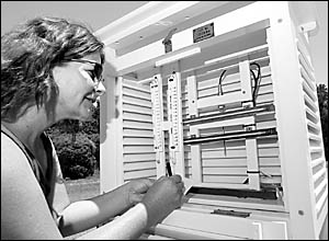 Duty observer Ashleigh Wilson checks the thermometers at the Coffs Harbour Meteorological Office