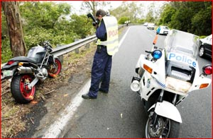 A police officer photographs the motorbike involved in a single-vehicle accident.
