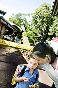 STORM DAMAGE: Five-year-old Kaleb Phillips is comforted by his mother, Cindy, of Lismore, outside the Lismore Transit Centre