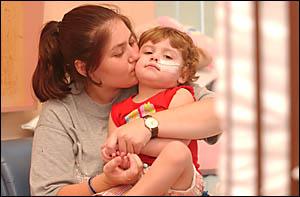 Grafton mother Melissa Harrison kisses her sick daughter Anna-lise