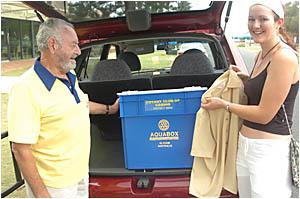 Yamba Rotarian Ralph Watson shows a town shopper an aquabox and clothing which will be sent to tsunami victims.