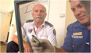 CRIME CHECK: Yamba Ambulance Station manager Alan Smith, left, watches as officer Richard Szlicht dusts for prints.