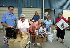 IKIN Store It storage company business development manager Ben Ikin and manager Jennie Hunter (back) help volunteers.