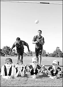Parramatta Eels players Dean Witters and Daniel Wagon with the ball boys for the game against Cronulla.