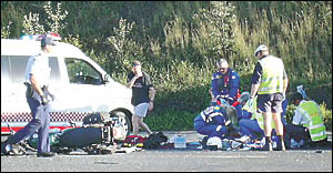 FRANTIC EFFORTS: Ambulance officers treat the injured motorcyclist at the crash scene on the Pacific Highway at St Helena.