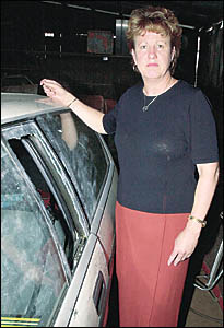 Detective Inspector Anne Langford, from the Richmond Local Area Command, stands beside one of the recovered cars