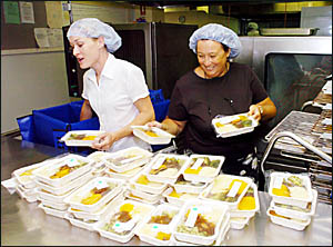 FULL UP: Samantha Pickford, left, and Cathie Eames prepare some of the 180 meals for dispatch at Lismore Base Hospital.