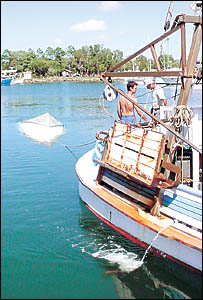TO THE RESCUE: Peter McHunter, left, skipper of trawler The Piper J, and deckhand Mike Wilkes, tow the upturned runabout