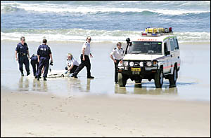 FATAL SHORE: Paramedics and police officers prepare to remove one of the bodies from Lennox Head?s Seven Mile Beach yesterday