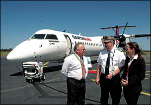 Pilot Manny Garyfalakis (centre) discusses the Q400 aircraft with Paul Kelly and Ashleigh Trouncer yesterday