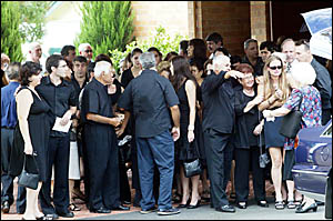 FAMILY and friends of Deon Chrisostomos comfort each other outside Murwillumbah?s All Saints Anglican Church.
