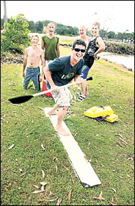Joe Kennard, centre, with the remains of his fishing boat which sunk on the Brunswick River bar, with his passengers.