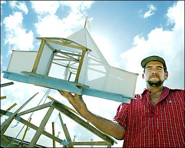 AAARTEC co-operative member Bill Marshall holds a model of the camphor-laurel big-top tent.