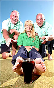 Yamba Bowling Club employee Debbie Booth, protects her black beer from fellow workers Allan Body and Barry Wiseman