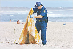 A crime scene officer from Lismore police examines a blanket at the alleged rape site at Clarks Beach, Byron Bay.