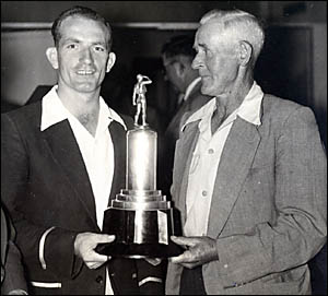 Keith Ellem (left) receiving the CRCA trophy for most wickets taken during the 1953-54 season, from Joe Ford.