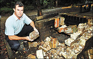 Community liaison forester for Forests NSW North East Region, David Wilson, with the vandalised brick barbecue.