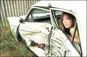 CAR TROUBLES: Sonya Want sits in her Falcon that was damaged when the webbing on the NRMA tow truck snapped