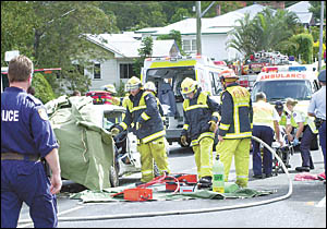 Police, fire and ambulance staff work to free an elderly man trapped in Lismore yesterday.